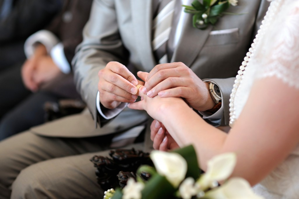 Groom putting a ring on bride's finger